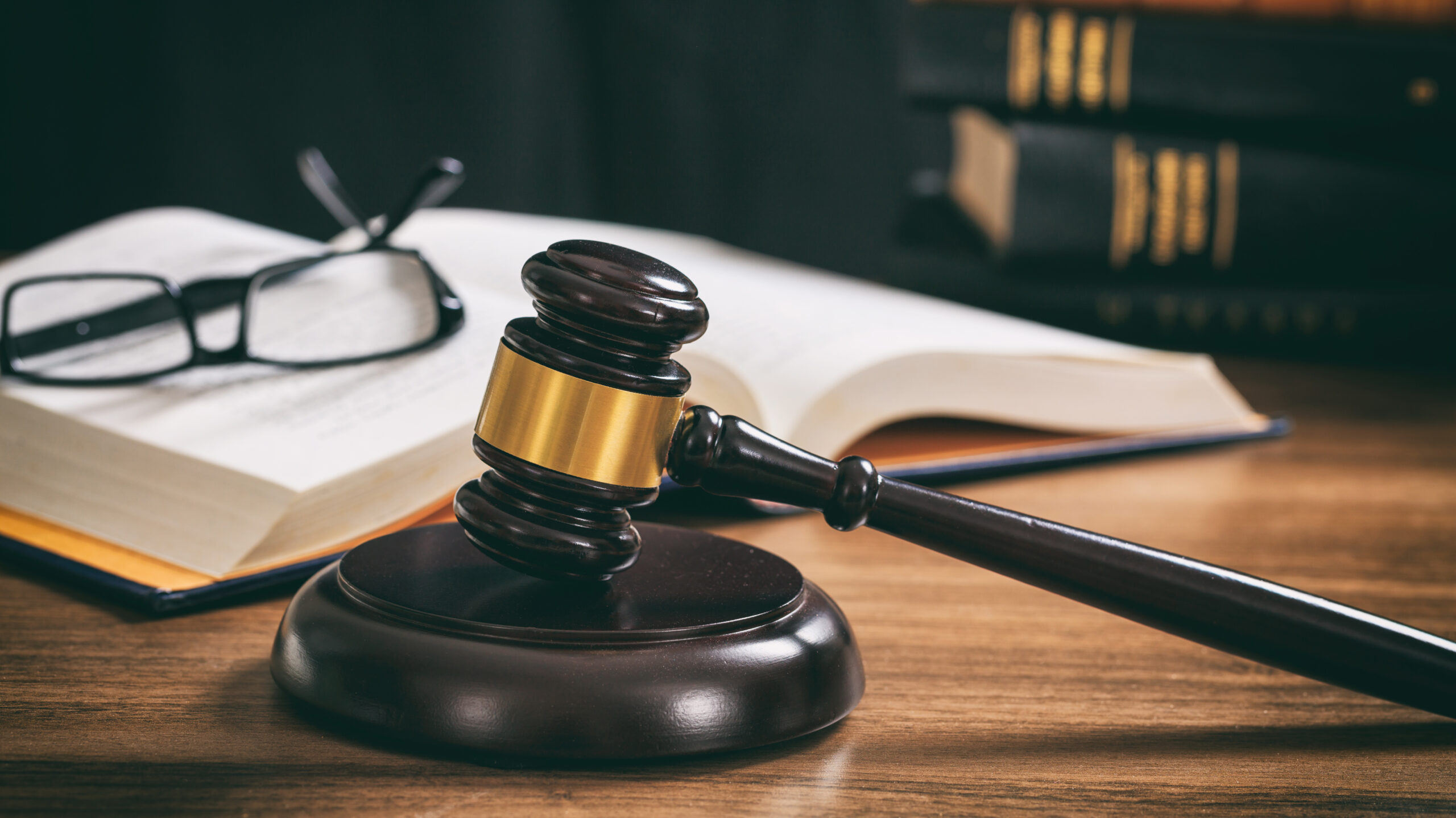 Law gavel on a wooden desk, law books background