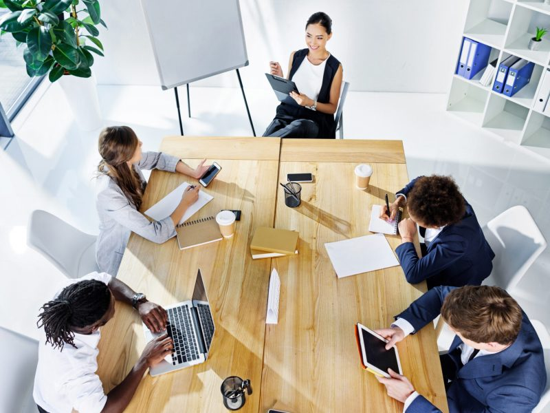 multicultural business people discussing new strategy at meeting in office